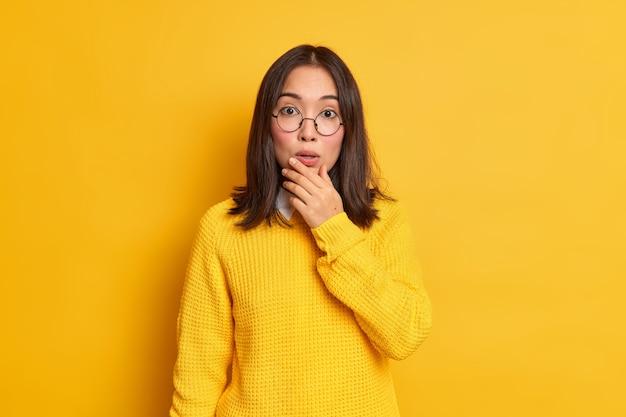印象的な美しいアジアの女性は、あごを持って唖然としているように見えます。衝撃的な何かが丸い眼鏡のカジュアルなセーターを着ているのを聞きます。