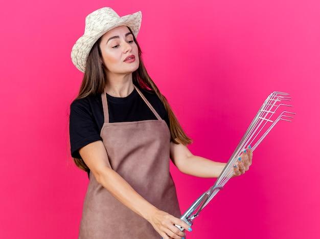 원예 모자를 들고 분홍색 배경에 고립 된 잎 갈퀴를보고 제복을 입은 아름다운 정원사 소녀 감동