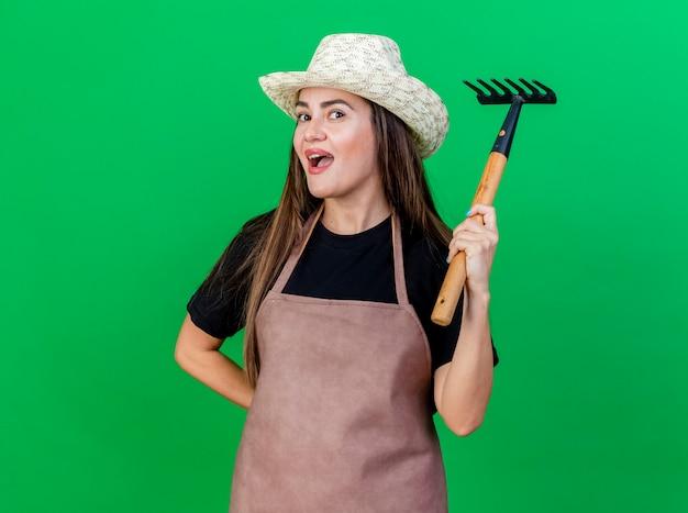Впечатлила красивая девушка-садовник в униформе в садовой шляпе, поднимающей грабли, изолированные на зеленом