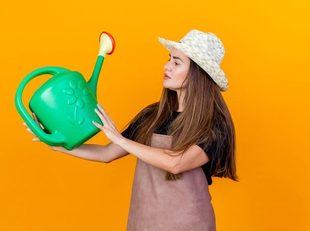 Impressionato bella ragazza giardiniere indossa uniforme e cappello da giardinaggio tenendo e guardando annaffiatoio isolato su sfondo arancione