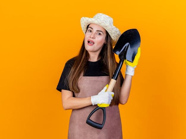 Impressionato bella ragazza giardiniere che indossa uniforme e cappello da giardinaggio con guanti che tengono vanga isolato su sfondo arancione