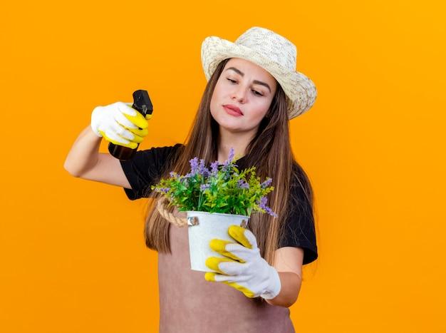 Bella ragazza giardiniera impressionata che indossa uniforme e cappello da giardinaggio