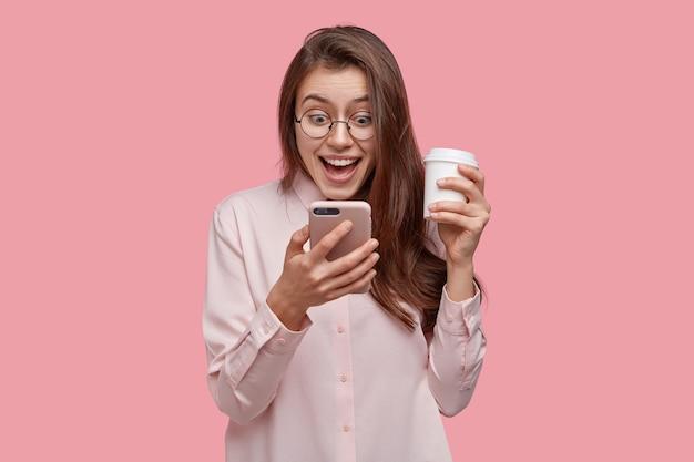 Впечатленная красивая женщина чувствует себя вне себя от радости, читает текстовое сообщение от волнения, официально одета, несет кофе на вынос, изолирована над розовой стеной студии. люди