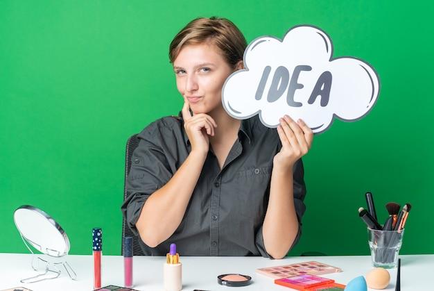 Una bella donna impressionata si siede al tavolo con strumenti per il trucco che tengono una bolla di idee con un pennello per il trucco che mette il dito sulla guancia