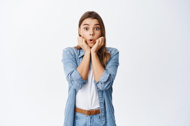 Impressionato modello femminile biondo ansimando e dicendo wow, appoggiandosi alle mani e fissando stupito davanti, controllando la pubblicità, in piedi sul muro bianco