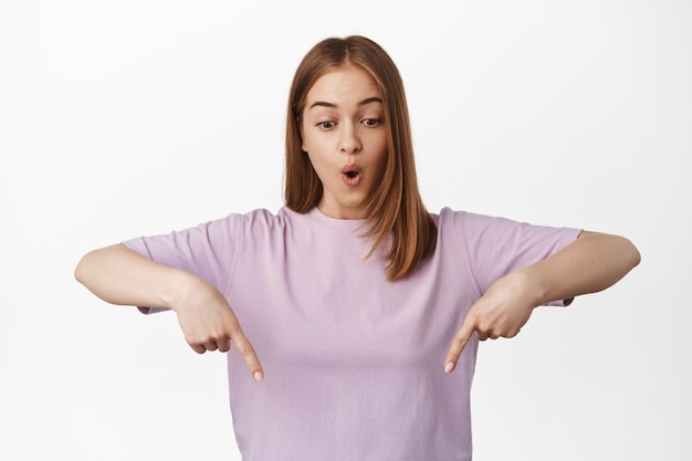 Impressed blond woman pointing down, looking at advertisement below with gasping surprised face, standing in t-shirt over white wall