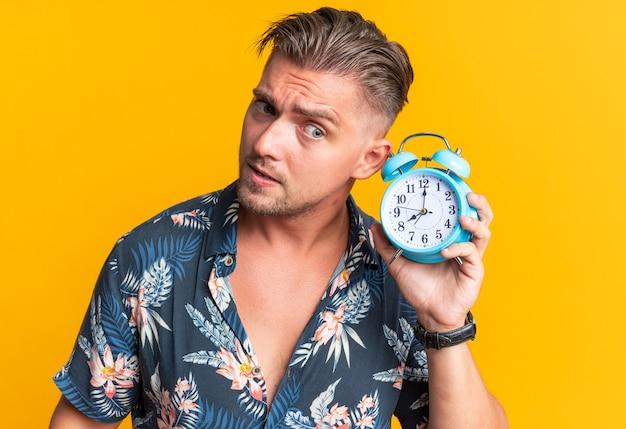 彼の耳の近くに目覚まし時計を保持している印象的な金髪のハンサムな男