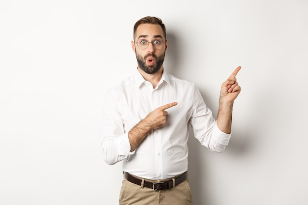 Impressed businessman showing interesting promo offer, pointing fingers right, standing amazed against white background.