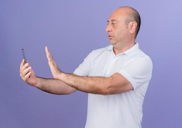 Впечатлен случайный зрелый бизнесмен, держащий и смотрящий на мобильный телефон и не делающий жестов, изолированных на фиолетовом фоне