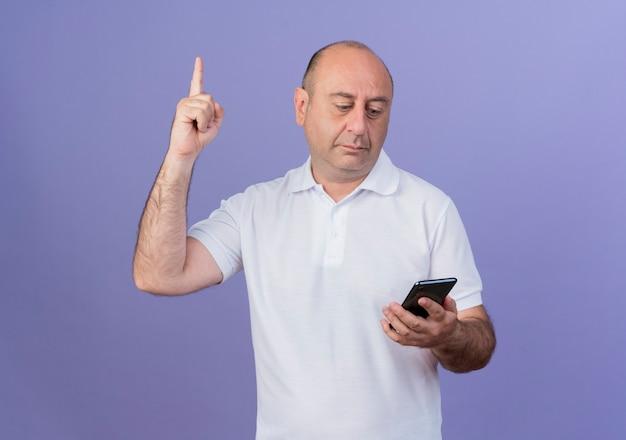 감동 된 캐주얼 성숙한 사업가 잡고 보라색 배경에 고립 된 손가락을 올리는 휴대 전화를보고