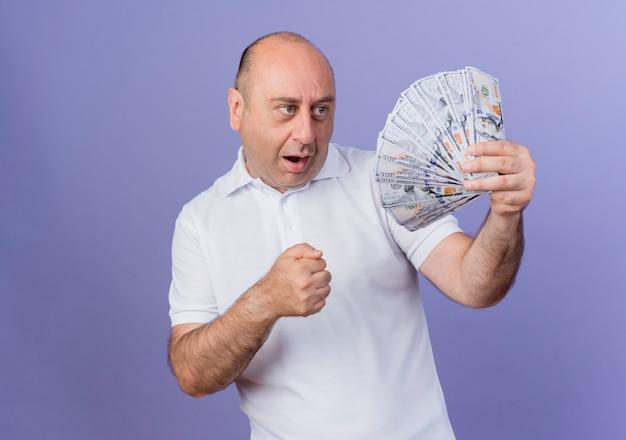 コピースペースで紫色の背景に分離されたお金と握りこぶしを握って見て感動カジュアル成熟したビジネスマン