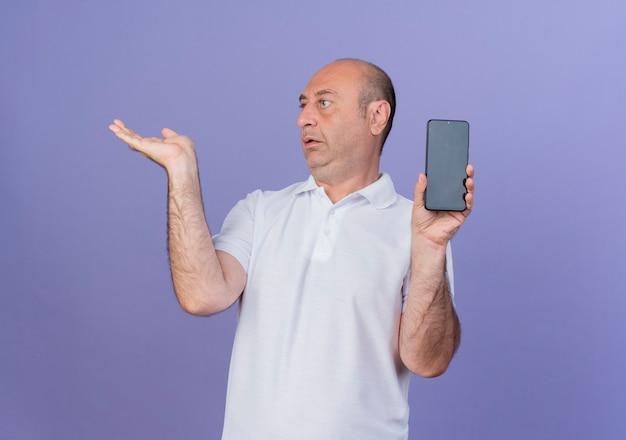 측면을보고 복사 공간이 보라색 배경에 고립 된 빈 손을 보여주는 휴대 전화를 들고 감동 캐주얼 성숙한 사업가