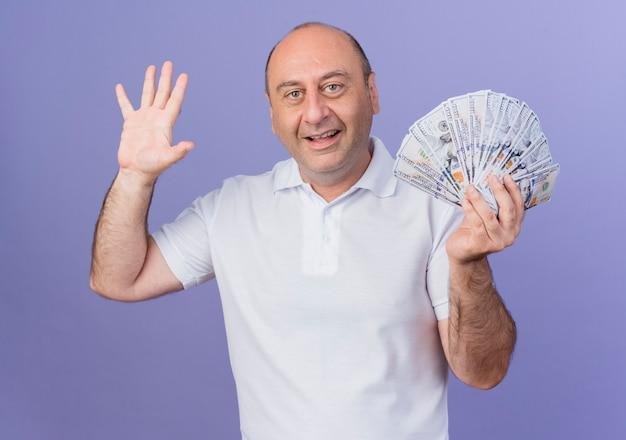 Впечатлен случайный зрелый бизнесмен, держащий деньги и делающий приветственный жест на камеру, изолированную на фиолетовом фоне