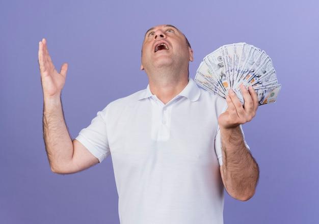 Впечатлен случайный зрелый бизнесмен, держащий деньги, держа руку в воздухе и смотрящий вверх, изолированный на фиолетовом фоне