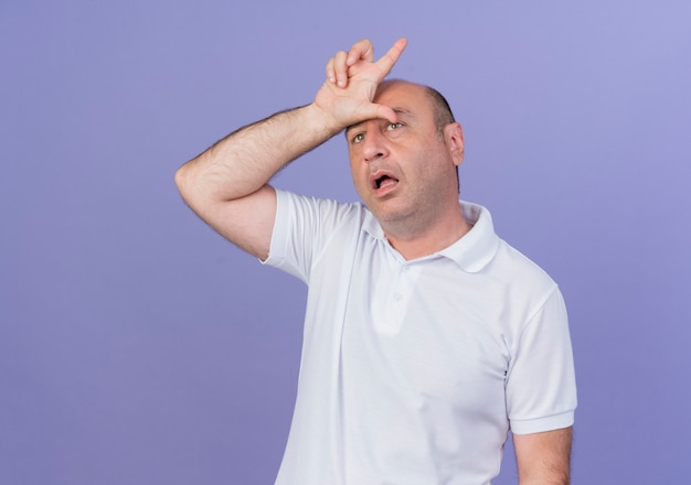 Impressed casual mature businessman looking straight putting hand on forehead doing loser gesture isolated on purple background with copy space