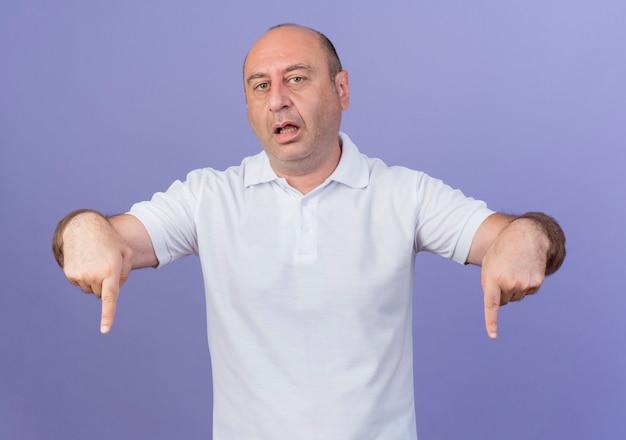 Впечатлен случайный зрелый бизнесмен, указывая вниз на фиолетовом фоне