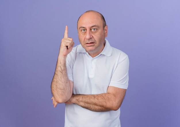 Impressed casual mature businessman putting hand under elbow and raising finger isolated on purple background with copy space