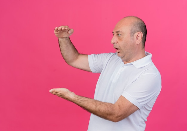 Impressed casual mature businessman standing in profile view looking straight showing size isolated on pink background with copy space
