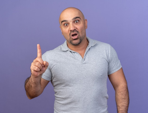 Impressed casual middle-aged man pointing up isolated on purple wall