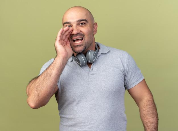 목에 헤드폰을 끼고 감명을 받은 캐주얼 중년 남성이 올리브 녹색 벽에 격리된 채 입 근처에 손을 대고 속삭였습니다.