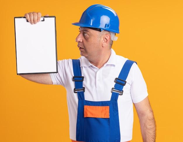 L'uomo adulto caucasico del costruttore impressionato in uniforme tiene ed esamina la lavagna per appunti sull'arancio