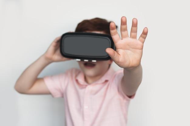 感動した白人の少年が白い壁でvrヘッドセットをテストしているときに何かに触れています