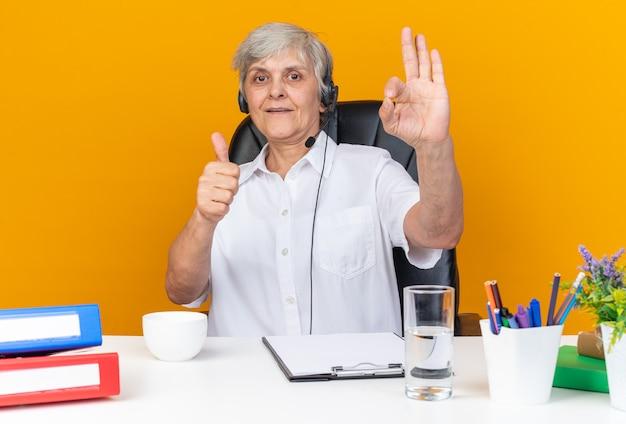 Impressionato operatore di call center femminile caucasico sulle cuffie seduto alla scrivania con gli strumenti dell'ufficio che sfogliano e gesticolano segno ok isolato sulla parete arancione