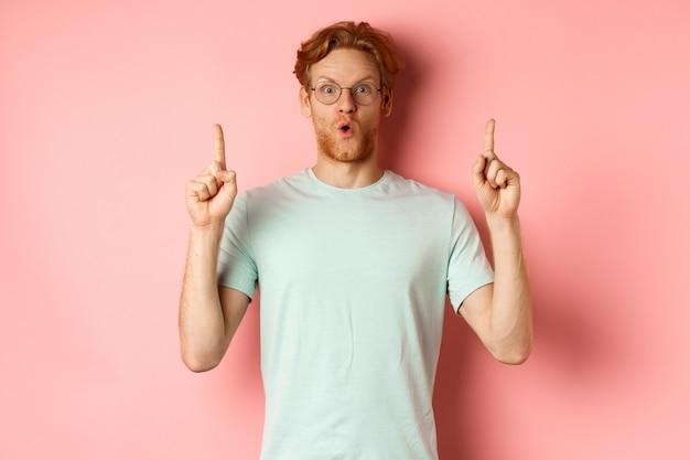 Впечатленный кавказский мужчина с рыжими волосами, в очках и футболке, стоящий на розовом фоне, здоровается и показывает пальцем на потрясающую сделку