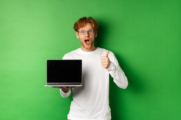 빨간 머리와 수염, 빈 노트북 화면과 엄지 손가락을 보여주는 인상적인 백인 남자, 카메라에 놀란 찾고, 온라인, 녹색 배경을 칭찬합니다.