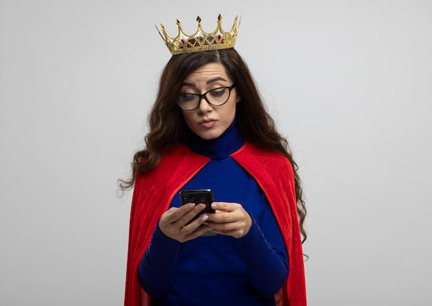 光学ガラスの王冠と赤いマントを持つ印象的な白人のスーパーヒーローの女の子は、コピースペースで白い壁に隔離された電話を保持し、見ています