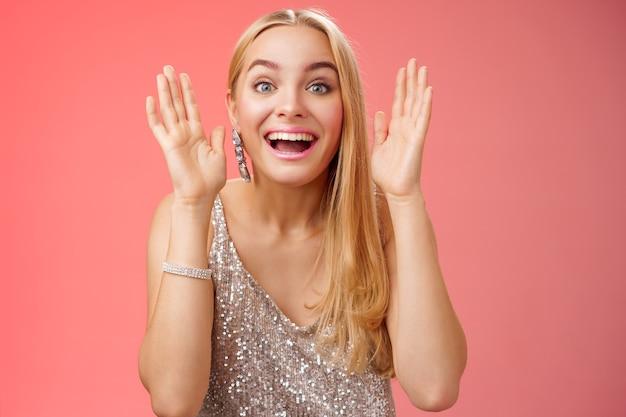 Impressionato affascinante intrattenuto donna bionda europea 25s in elegante abito glamour argento divertirsi giocando a cucù sorridente con gioia tenere i palmi vicino al viso ridere divertito, in piedi sfondo rosso