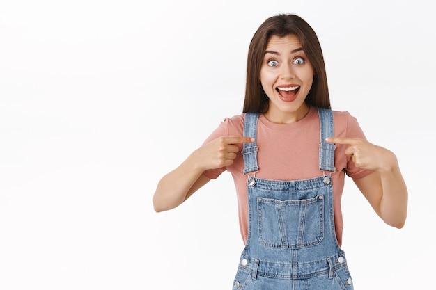 Impressionata, allegra donna bruna entusiasta in salopette di jeans, t-shirt, che si indica con un'espressione stupita e sorpresa, sorridendo ampiamente, è stata scelta, vincendo, riceve un premio, sfondo bianco