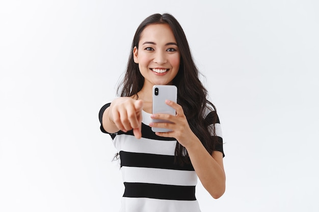 Impressed, cheerful young excited female tourist in casual outfit, holding smartphone and pointing forward as record funny event, smiling entertained, photographing, white background