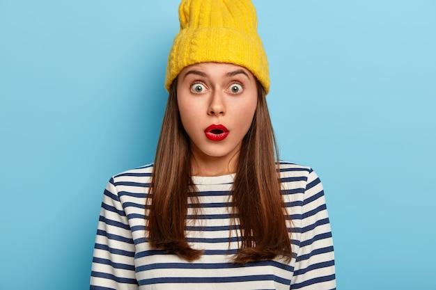 Впечатленная обеспокоенная женщина реагирует на ошеломляющий слух, задерживает дыхание, глаза прикованы, носит желтую шляпу и полосатый джемпер, не верит удивленным новостям, у нее красные губы, минимальный макияж