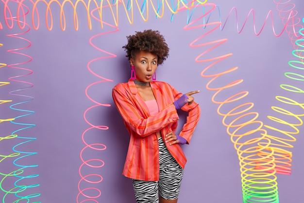 La donna dalla pelle scura impressionata indica da parte l'espressione scioccata, sta con la bocca aperta, indossa giacca alla moda, guanti sportivi e leggings