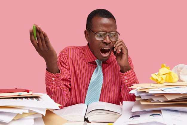 L'uomo dalla pelle scura arrabbiato e deluso impressionato cerca di risolvere il problema e trova una soluzione durante la conversazione telefonica, urla forte, vestito con una camicia formale