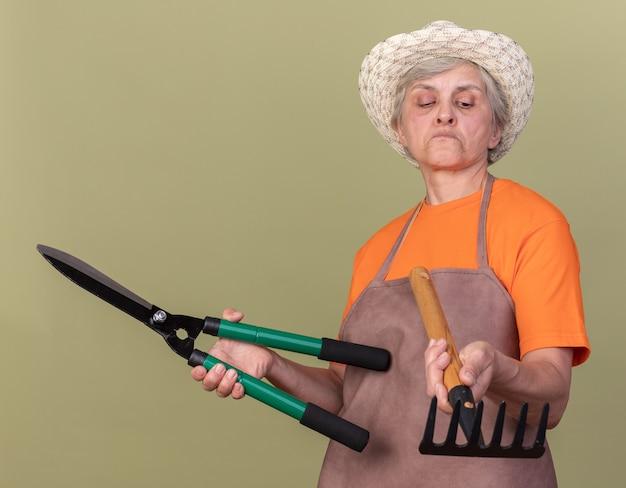 ガーデニングはさみを保持し、コピースペースでオリーブグリーンの壁に分離されたレーキを見てガーデニング帽子をかぶって感動した年配の女性の庭師