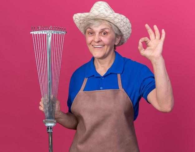 잎 갈퀴를 들고 확인 표시를 몸짓으로 원예 모자를 쓰고 감동 된 노인 여성 정원사