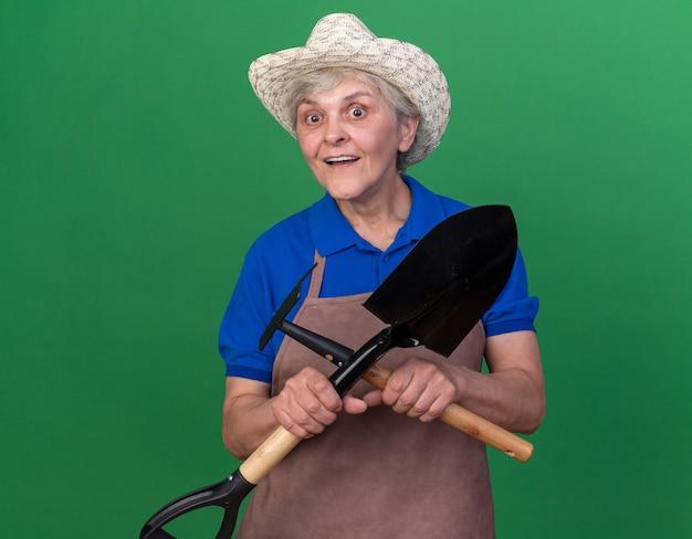 복사 공간이 있는 녹색 벽에 격리된 갈퀴와 스페이드를 들고 원예용 모자를 쓴 노인 여성 정원사