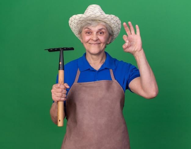 Colpito anziano giardiniere femmina indossando giardinaggio hat holding rastrello e gesticolando segno ok isolato sulla parete verde con spazio di copia