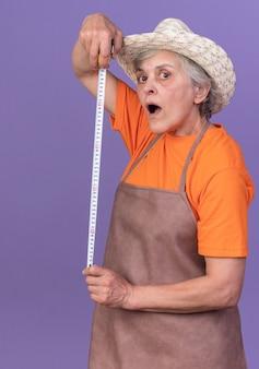 Impressionato giardiniere donna anziana che indossa un cappello da giardinaggio che tiene il metro a nastro
