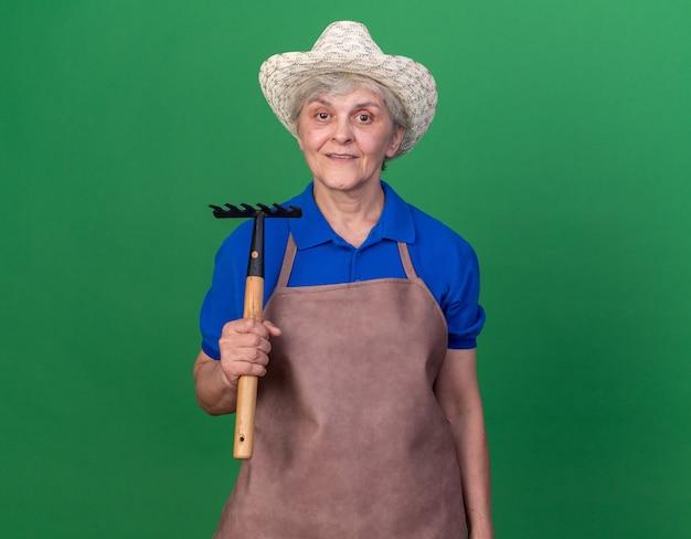 Il giardiniere femminile anziano impressionato che porta il cappello di giardinaggio tiene il rastrello
