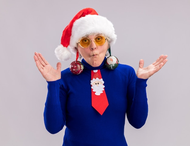 サンタの帽子とサンタのネクタイとサングラスで感銘を受けた年配の女性は、耳にガラス玉の飾りを保持し、手を開いたままにします