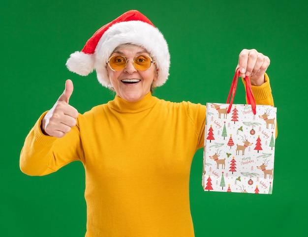 Впечатленная пожилая женщина в солнцезащитных очках в шляпе санта-клауса держит бумажный подарочный пакет и большие пальцы руки вверх изолирована на зеленом фоне с копией пространства