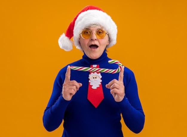 Donna anziana impressionata in occhiali da sole con cappello da babbo natale e cravatta di babbo natale che tiene un bastoncino di zucchero isolato su una parete arancione con spazio per le copie