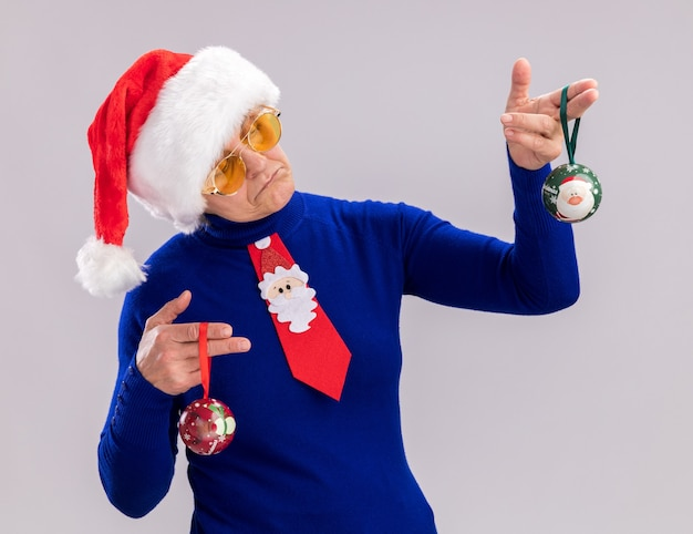 Impressed elderly woman in sun glasses with santa hat and santa tie holding and looking at glass ball ornaments isolated on white wall with copy space