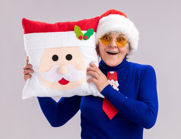 Impressed elderly woman in sun glasses with santa hat and santa tie holding santa pillow isolated on white wall with copy space