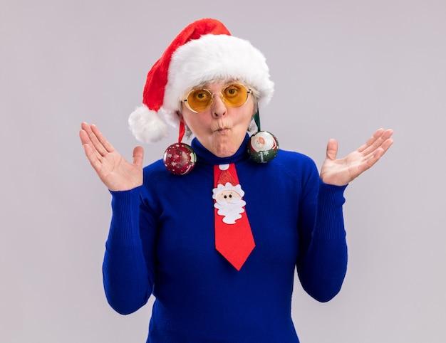 Impressionato donna anziana in occhiali da sole con cappello da babbo natale e cravatta a babbo natale tiene ornamenti palla di vetro sulle orecchie e tiene le mani aperte