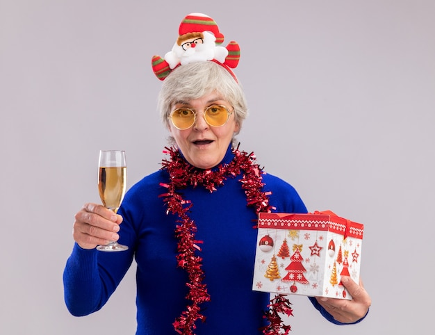 Impressed elderly woman in sun glasses with santa headband and garland around neck holds glass of champagne and christmas gift box isolated on white wall with copy space