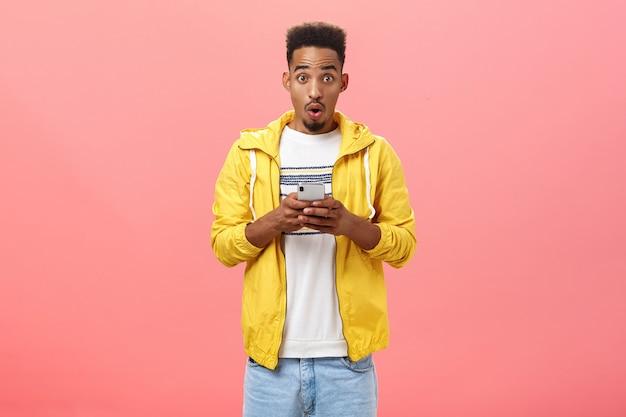 ピンクの壁の上のクールなデバイスの機能や新しいアプリで興奮して興奮しているスマートフォンを保持しているすごい音で巻き毛のヘアカット折りたたみ唇を持つ感動した熱狂的なアフリカ系アメリカ人の男性